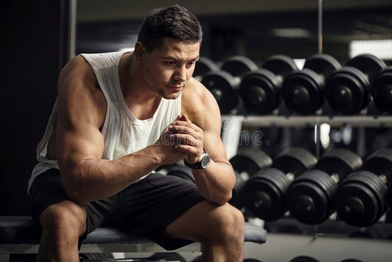 Заботливый серьезный спортсмен сидя в спортзале стоковое фото rf