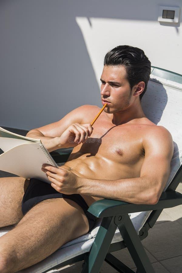 Заботливый топлесс молодой человек в deckchair с карандашем и тетрадью стоковое фото