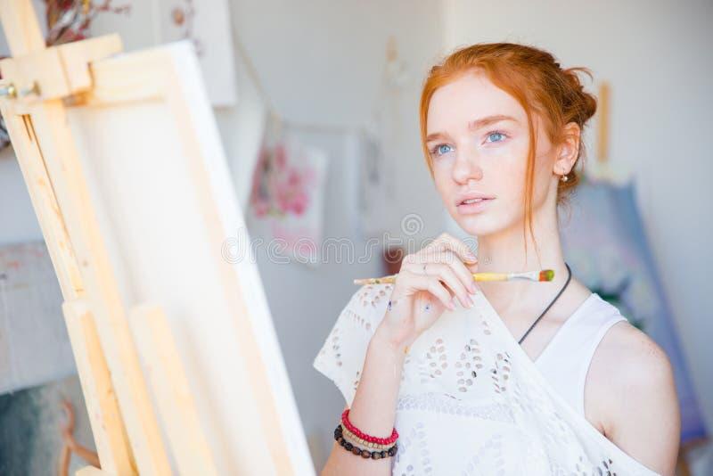 Заботливый художник женщины стоя перед мольбертом с paintbrush стоковое изображение
