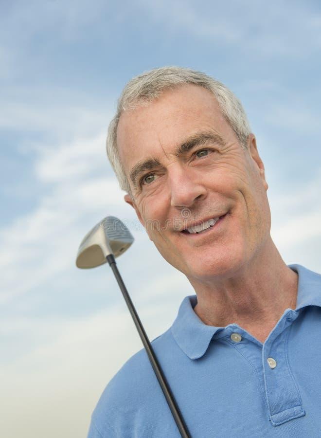 Заботливый человек с гольф-клубом против неба стоковая фотография rf