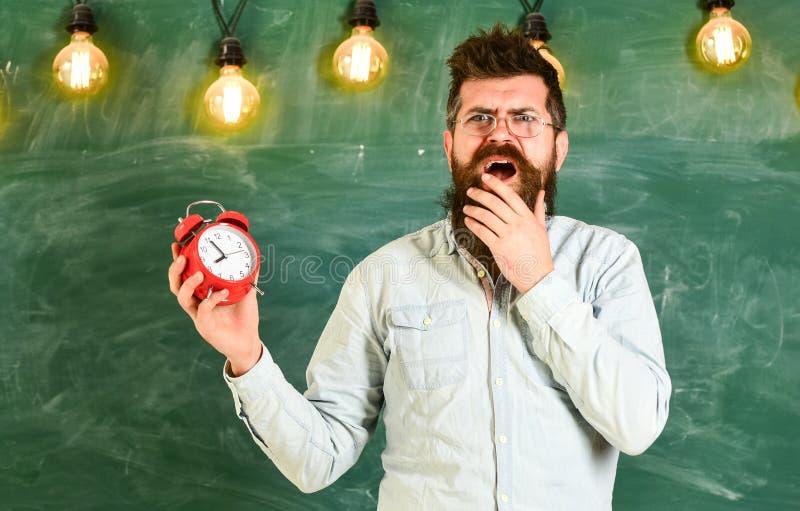 Забыл о концепции времени Бородатый битник держит часы, доску на предпосылке, космосе экземпляра Учитель в eyeglasses стоковые изображения