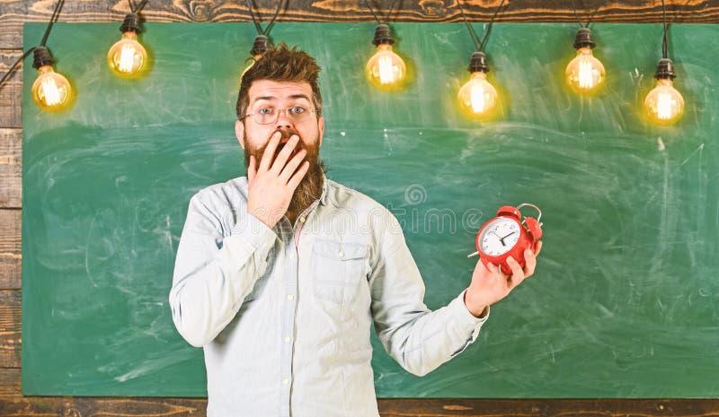 Забыл о концепции времени Человек с бородой и усик на сотрясенной стороне в классе Бородатый битник держит часы стоковые фото