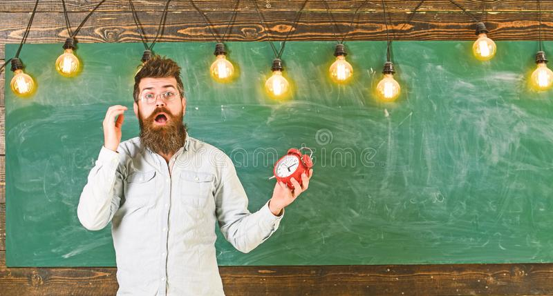 Забыл о концепции времени Человек с бородой и усик на сотрясенной стороне в классе Учитель в eyeglasses держит сигнал тревоги стоковое фото rf