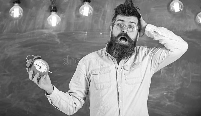 Забыл о концепции времени Человек с бородой и усик на confused выражении стороны в классе Портрет занятого стоковая фотография