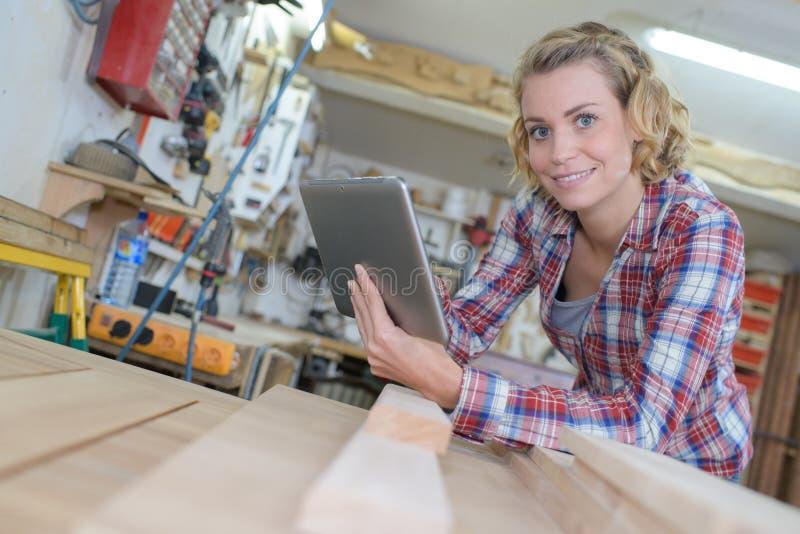 Заведущая держа цифровую таблетку в мастерской стоковое изображение