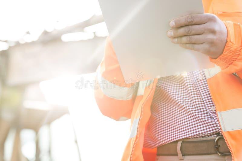 Заведущая Midsection держа доску сзажимом для бумаги на строительной площадке на солнечный день стоковая фотография rf