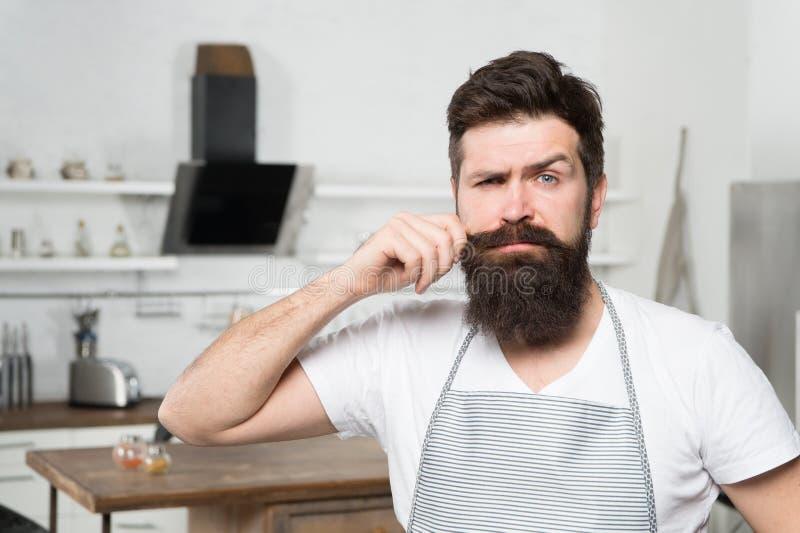 Завивать его длинный усик Профессиональный повар уверенный в его варя навыках Бородатый человек во время варить в кухне стоковые изображения rf