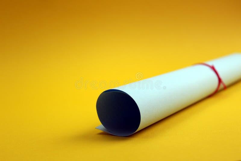завитая бумага прикрепила с красным потоком на желтой предпосылке стоковые изображения