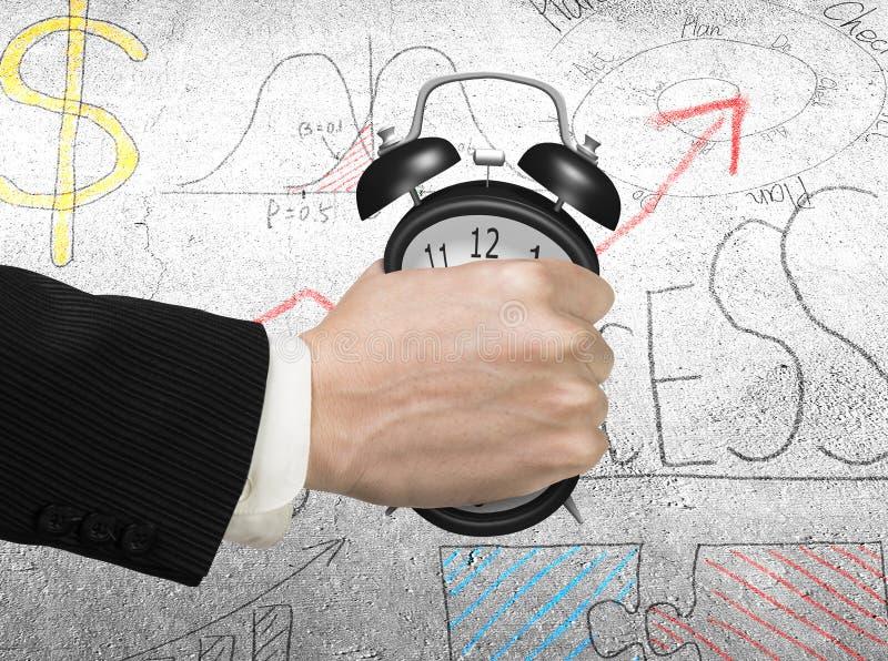 Завладевать концепцию времени Будильник удерживания руки человека стоковая фотография
