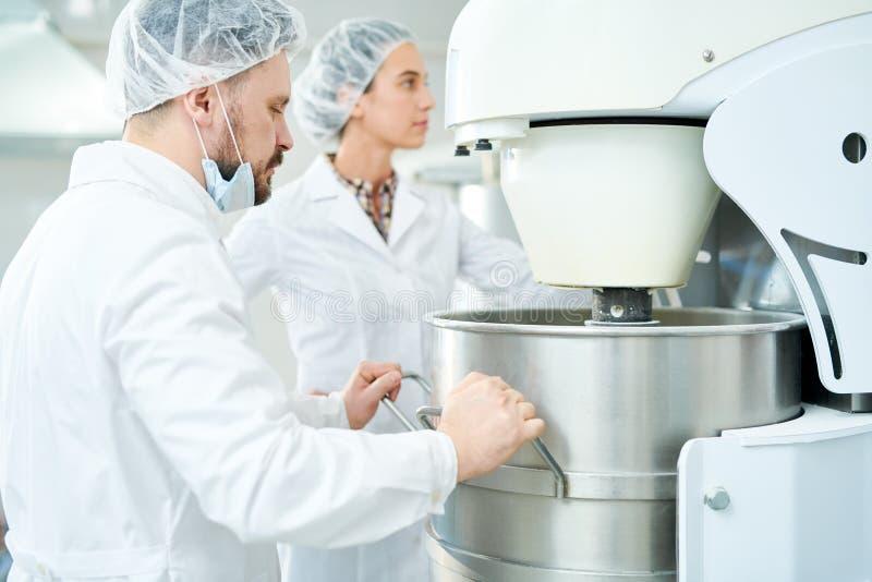 2 заводской рабочий кондитерскаи работая машинное оборудование стоковое изображение
