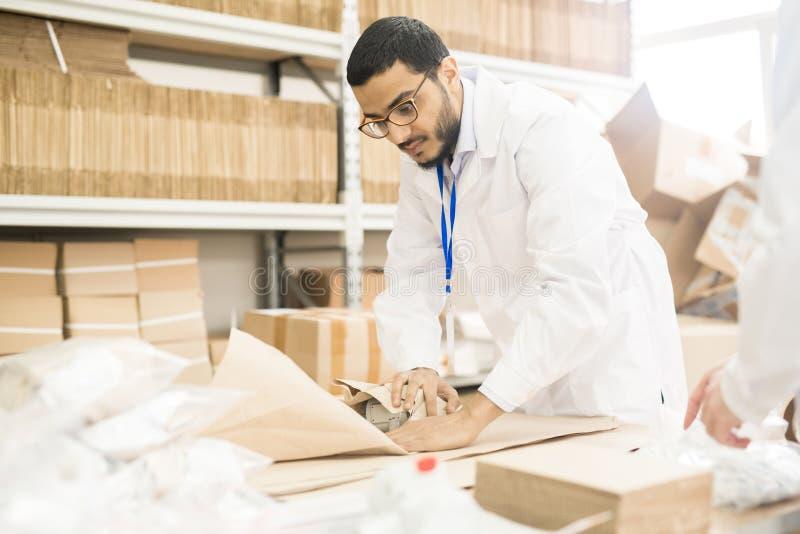 Заводской рабочий оборачивая манометр в бумаге стоковое фото