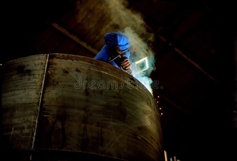 Заводской рабочий сваривая танк стоковая фотография rf