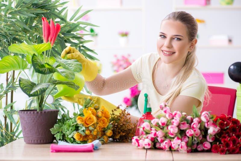 Заводы молодой женщины моча в ее саде стоковое фото