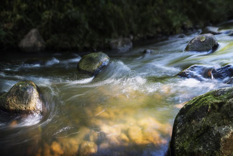 Заводь с камнями и малыми речными порогами потока, ровной водой мимо длиной стоковое фото