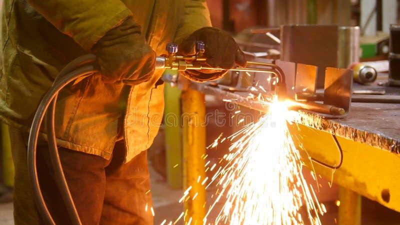Завод конструкции Человек на его рабочем месте используя сварочный аппарат Топление вверх сторона детали Sparkles огня стоковые фото