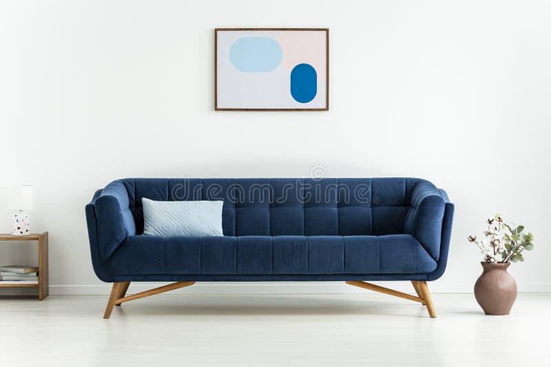 Завод рядом с голубым settee с валиком в белом минимальном интерьере живущей комнаты с плакатом Реальное фото стоковое изображение rf
