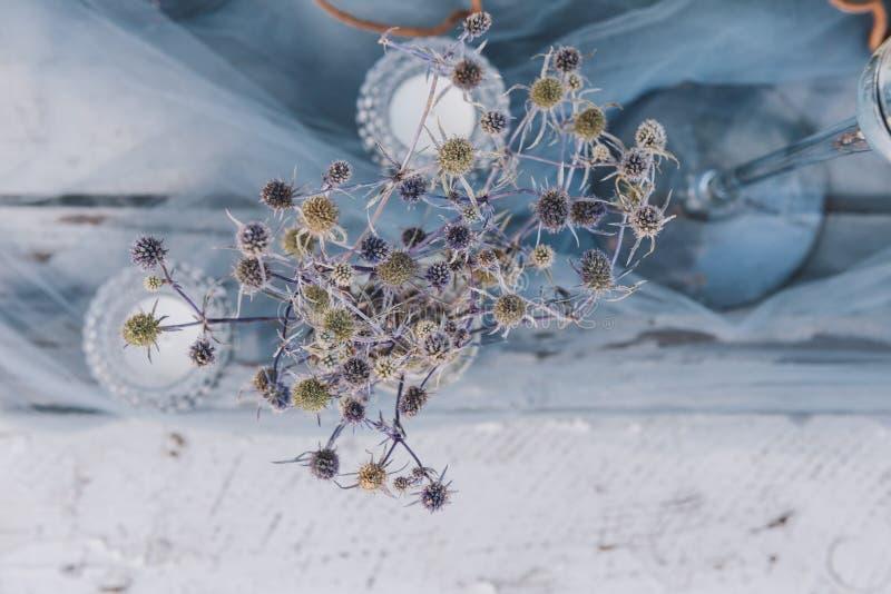 Завод, свечи чая и отвесная голубая ткань как часть установки таблицы  стоковые фото