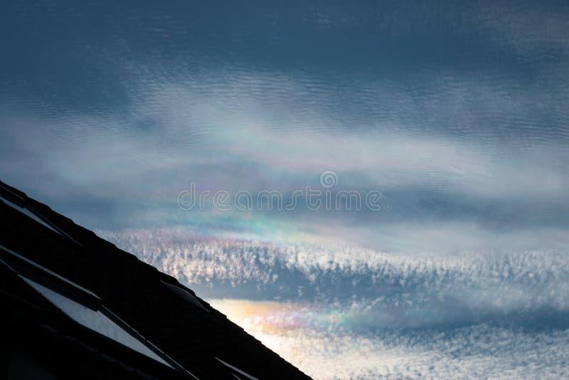 заволакивает радужное Иризация близко к солнцу в тонких облаках altocumulus и циррокумулуса стоковые фото