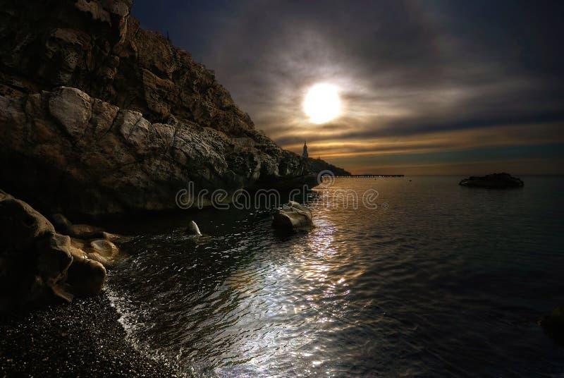 заволакивает солнце камней моря