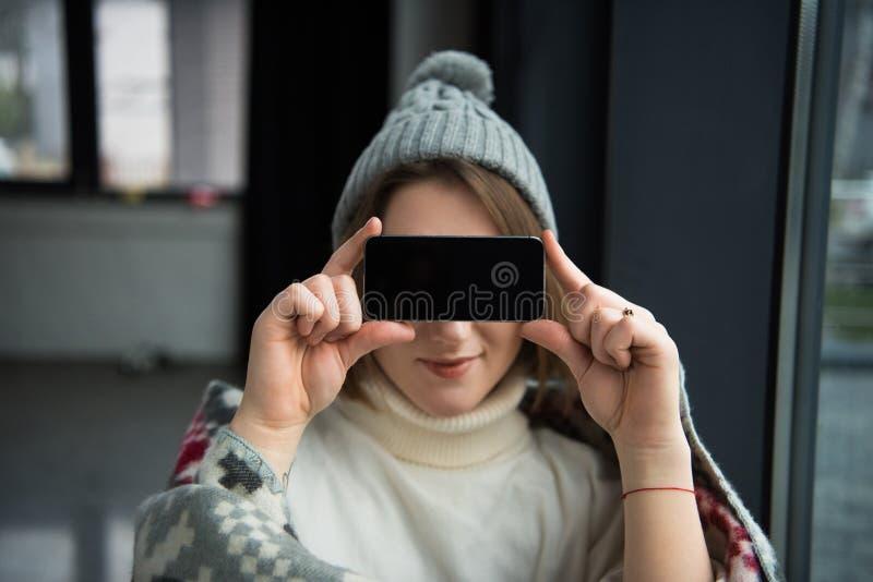 Заволакивание женщины наблюдает с smartphone стоковая фотография rf