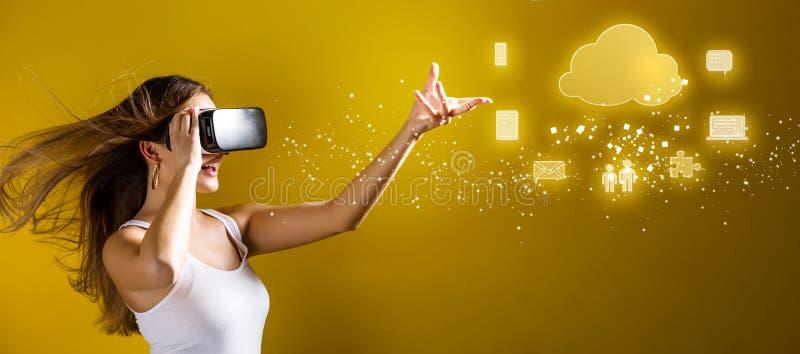 Заволоките вычислять при женщина используя шлемофон виртуальной реальности стоковая фотография