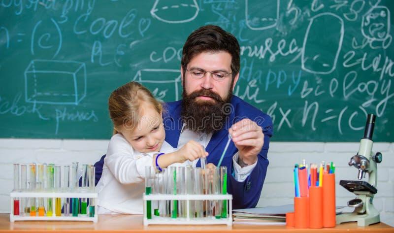 Завораживающий урок химии Учитель и зрачок человека бородатые с пробирками в классе Частный урок E стоковое изображение rf