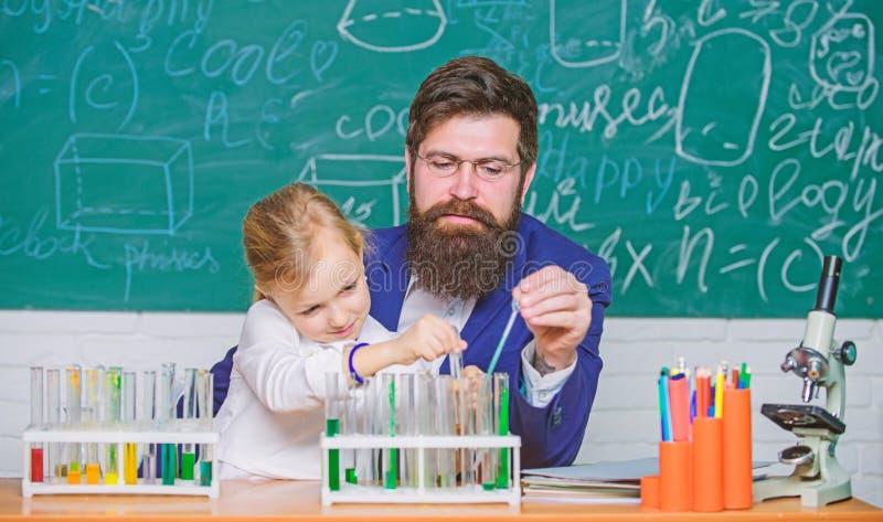 Завораживающий урок химии Учитель и зрачок человека бородатые с пробирками в классе Частный урок E стоковая фотография