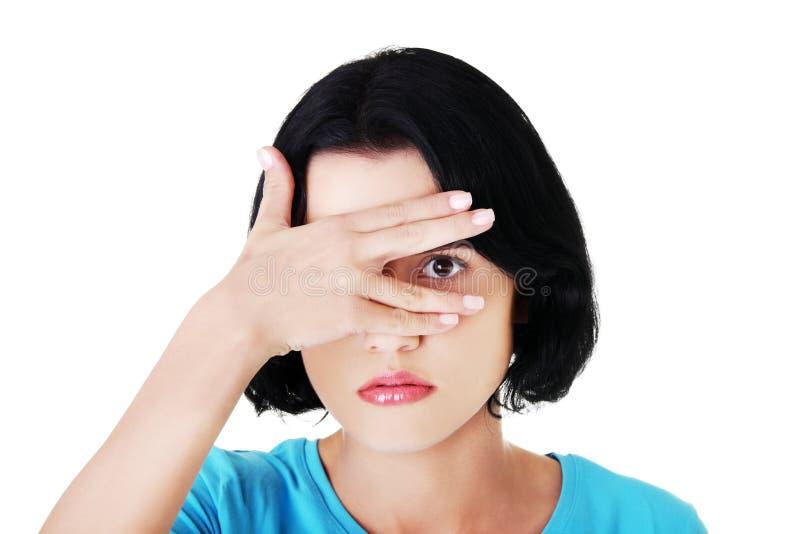 Заволакивание женщины портрета наблюдает из-за стыда стоковые фото