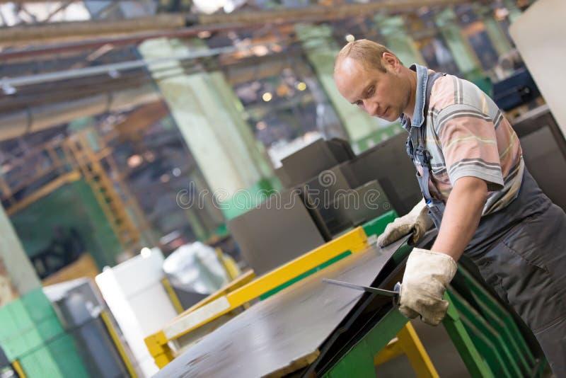 Заводской рабочий извлекая заусенцы металла от стального листа стоковое фото