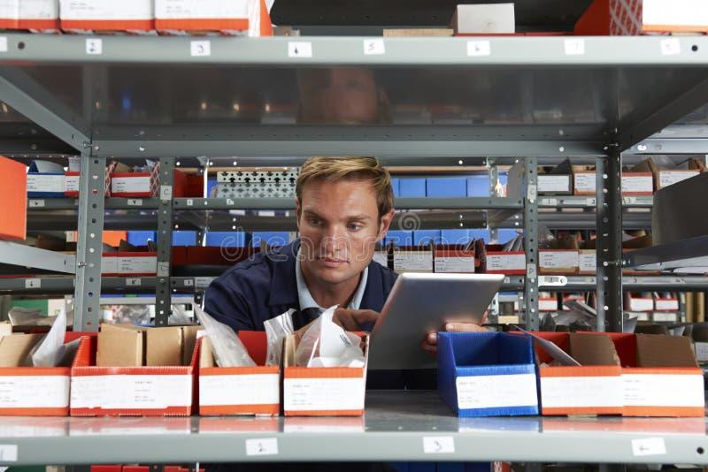 Заводской рабочий используя таблетку цифров в кладовой стоковая фотография