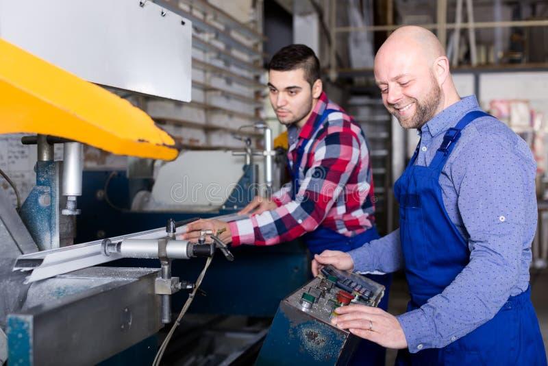 Заводской рабочий режа алюминиевые рамки стоковые изображения