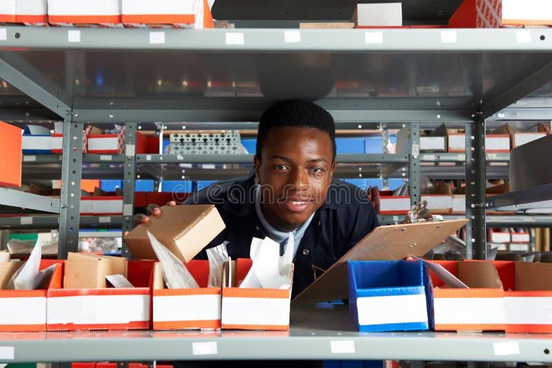 Заводской рабочий с доской сзажимом для бумаги в складе стоковое фото