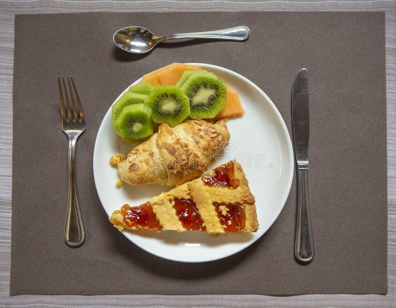 Завтрак: блюдо с домом сделало плодоовощ пирога, круассана, дыни и кивиа варенья стоковое изображение