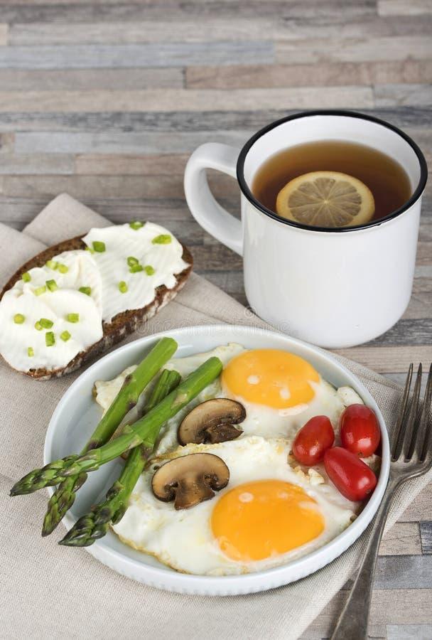 Завтрак взбитые яйца, спаржа, champignons, томаты вишни, сэндвич и чай лимона стоковое фото rf