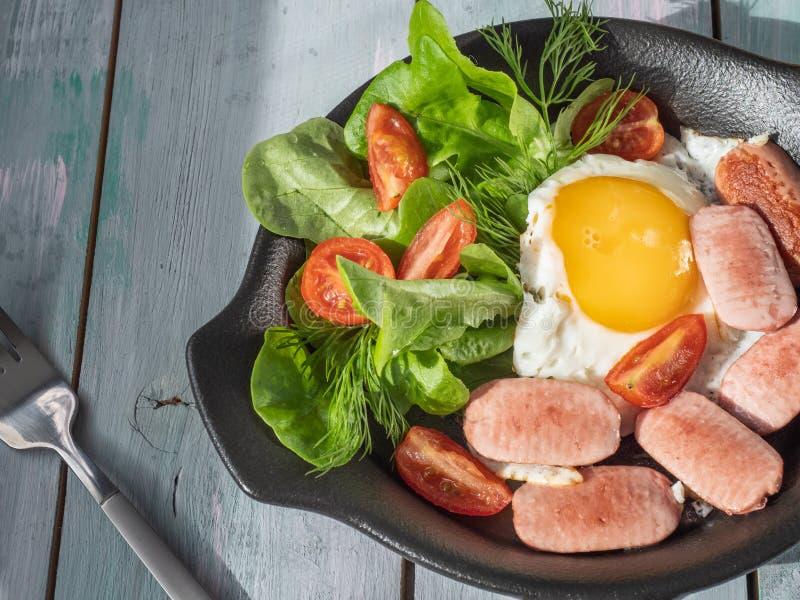 Завтрак взбитых яя с сосисками, томаты и салат лист в черной сковороде Подача на деревянный поднос планки с стоковое изображение
