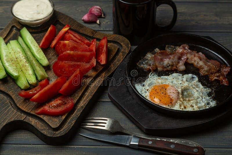 Завтрак-взболтанные яйца, соус чеснока, томаты, огурцы, бекон и кофе r стоковые фото