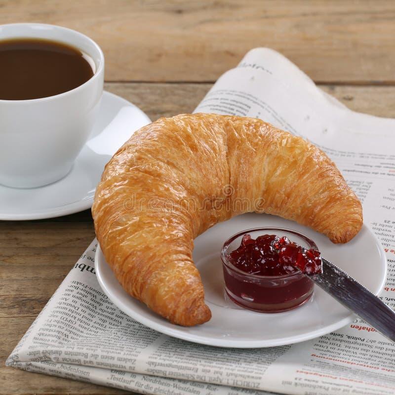 Завтрак дела с круассаном, кофе и газетой стоковое изображение