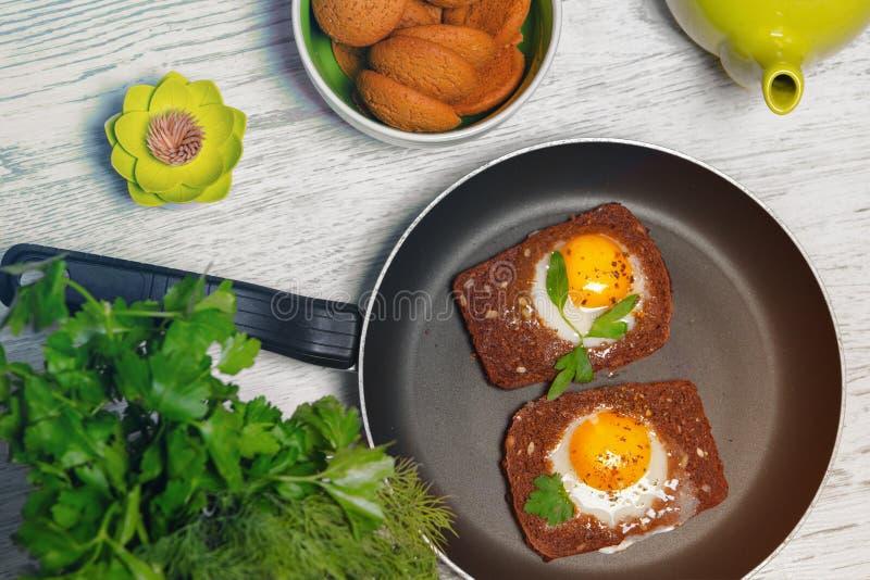 Завтрак - здравица с томатом, яичницами, яичницами, чайником и чашкой чаю обрабатываемого сыра на серой предпосылке стоковые фотографии rf