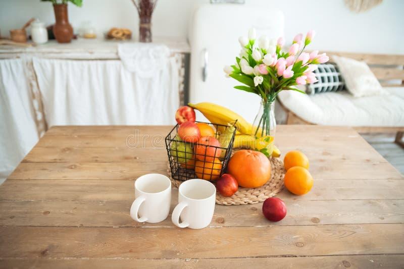 Завтрак концепции сделанный из плодов и кофе или чая Апельсины, бананы, чашки, персики на текстурном большом деревянном столе про стоковые фотографии rf