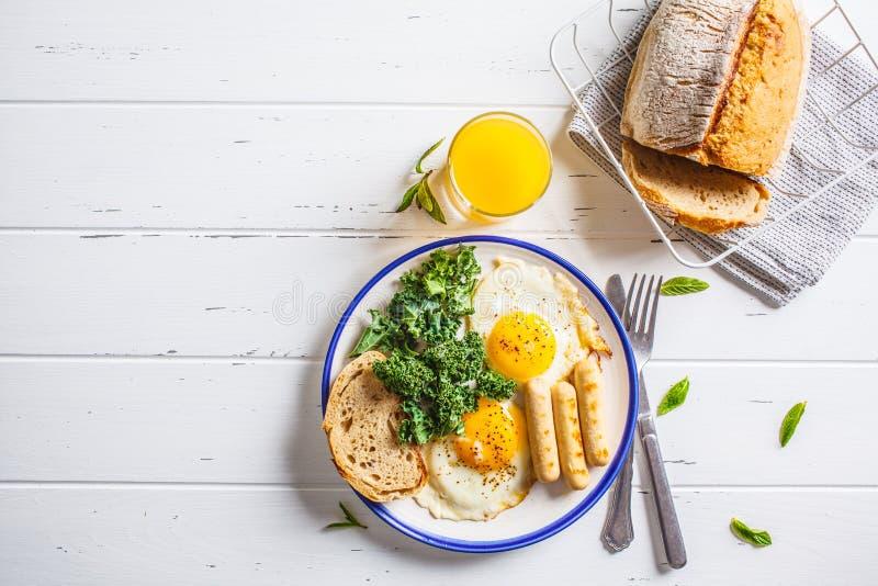 Завтрак, который служат с яичницами, салатом, булочками и оранжевым juic стоковые фото