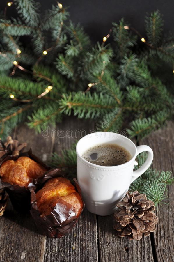 Завтрак рождества 2 пирожных и чашки горячего кофе на деревянном столе, на предпосылке ветвей ели со светами стоковые изображения