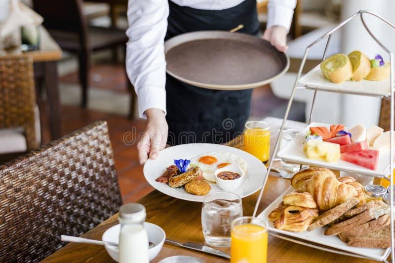 Завтрак сервировки официантки на ресторане стоковая фотография