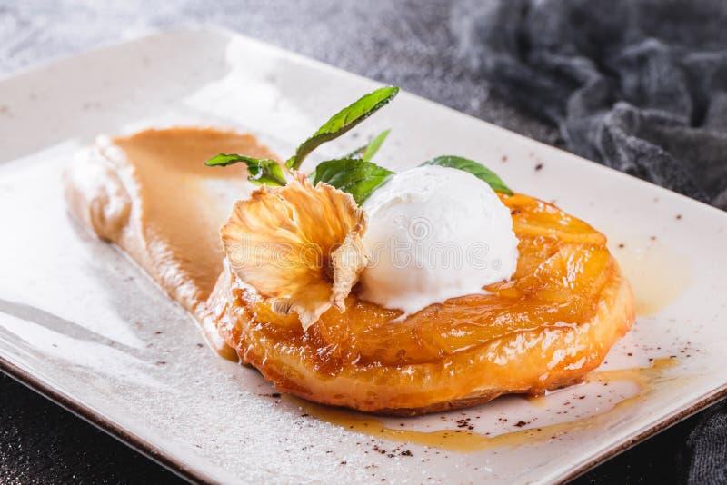 Завтрак со штруделью очень вкусного яблока с ананасом, вареньем, мороженым гарнированным с мятой и напудренным сахаром на тонкой  стоковая фотография rf