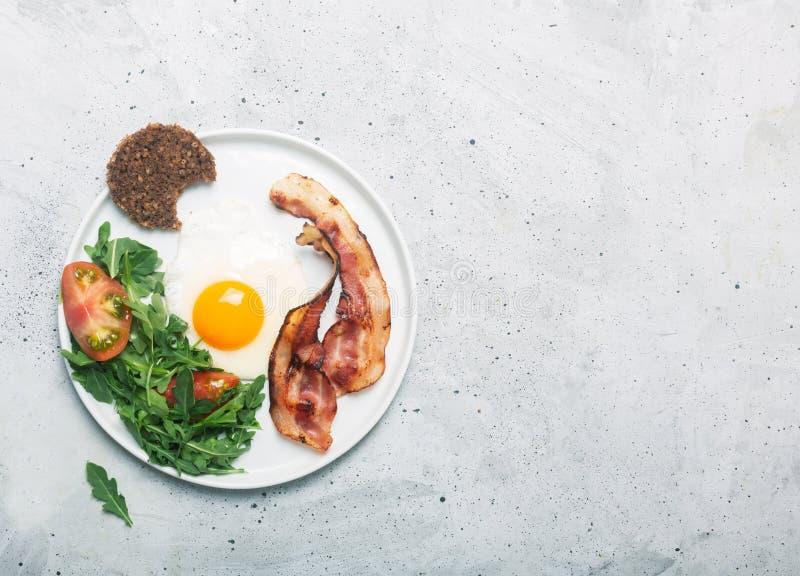 Завтрак стиля сердечного высоко- протеина английский с яйцом, зажаренным беконом и arugula на плите Взгляд сверху, горизонтальная стоковые изображения rf