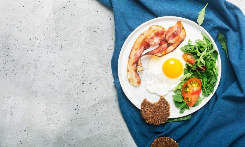 Завтрак стиля сердечного высоко- протеина английский с яйцом, зажаренным беконом и arugula на плите Взгляд сверху, горизонтальная стоковое фото