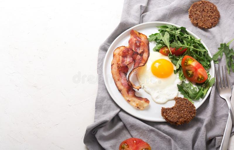 Завтрак стиля сердечного высоко- протеина английский с яйцом, зажаренным беконом и arugula на плите Взгляд сверху, горизонтальная стоковая фотография rf