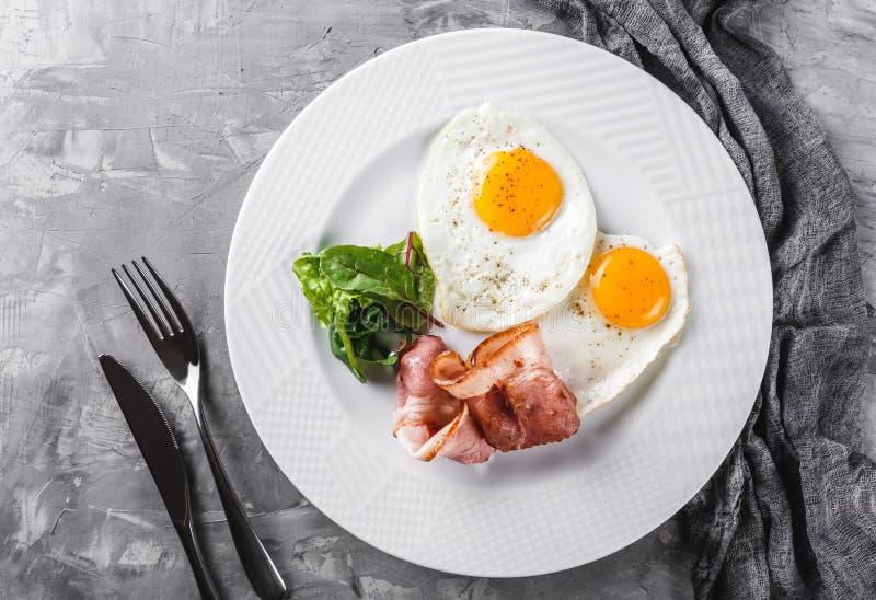 Завтрак, яичницы, бекон, ветчина, свежий салат на плите на серой поверхности таблицы Здоровая еда, взгляд сверху, плоское положен стоковая фотография