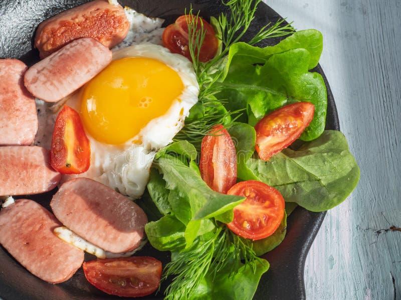 Завтрак яичниц с сосисками, томатами вишни и густолиственным салатом на черном круглом лотке Подача на деревянный поднос планки с стоковая фотография rf