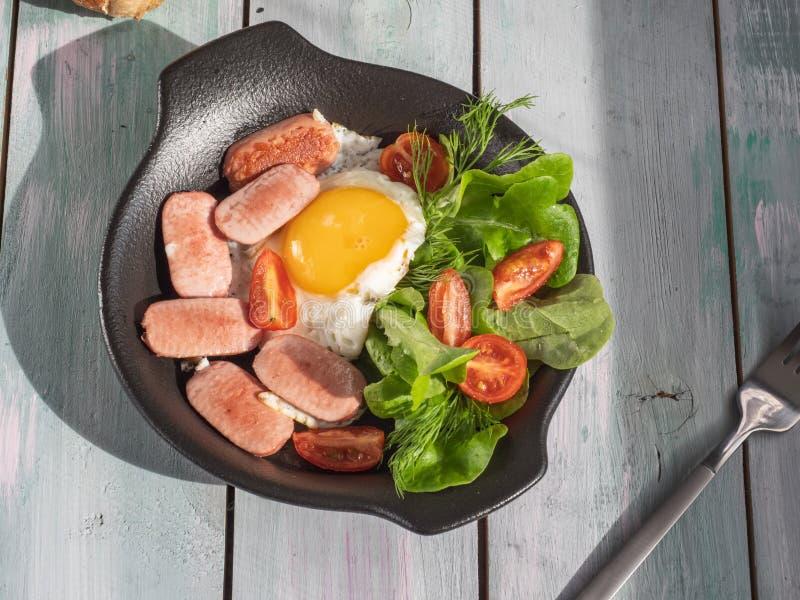 Завтрак яичниц с сосисками, томатами вишни и густолиственным салатом на черном круглом лотке Подача на деревянный поднос планки с стоковое фото