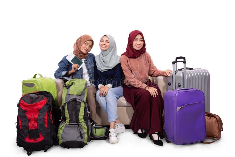 3 завуалированный путешественниками чемодан удерживания женщины в шутку сидя на кресле стоковая фотография